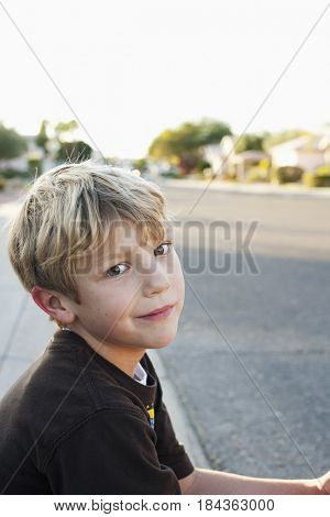 Caucasian boy sitting on curb