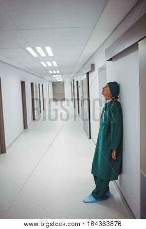 Tensed female surgeon leaning on wall in corridor of hospital