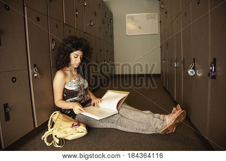 Middle Eastern teenager studying in locker room