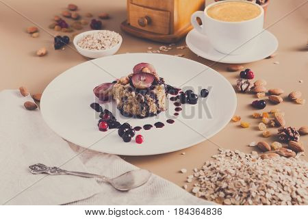 Healthy breakfast, dieting and detox concept - wholegrain fresh oatmeal porridge on plate with fruits, berries and nuts, morning coffee on background. Still life, shallow depth of field