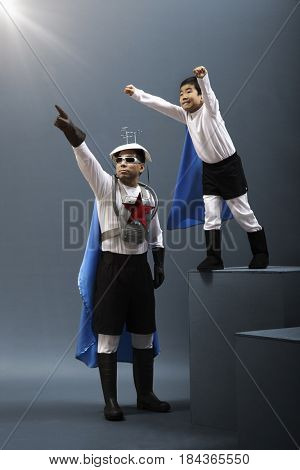 Korean boy in superhero costume flying while father watches