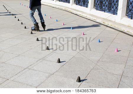 Roller skater practicing slalom along a line of cones.
