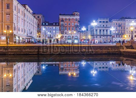 Trieste - December 2016, Italy: Night view of Trieste, old buildings mirror reflected in water, Grand Canal in Trieste city center