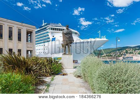 Trieste - August 2016, Friuli Venezia Giulia region, Italy: Harbor of Trieste, monument of Nazario Sauro, bronze statue of the famous sailor with cruise ship and blue sky on the background