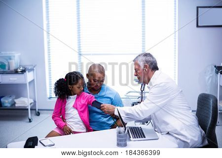 Doctor checking patient blood pressure in clinic