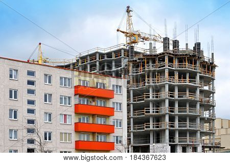The process of construction of multistory monolithic building. Concrete and metal frame of floor slabs and columns. Residential house with orange balconies in the foreground.