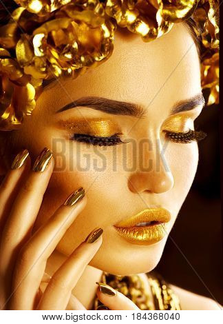 Gold Woman face holiday makeup. Beauty fashion model girl with Golden make up, hair and jewellery on glowing background. Gold wreath and necklace. Fashion art portrait, Hairstyle, manicure and make up