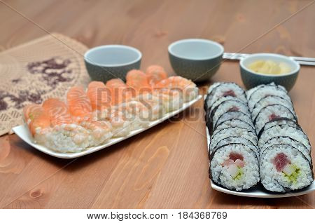 Plates Of Maki Sushi Rolls And Nigiri Sushi With Salmon And Shrimp Japan Food On The Table With Soy