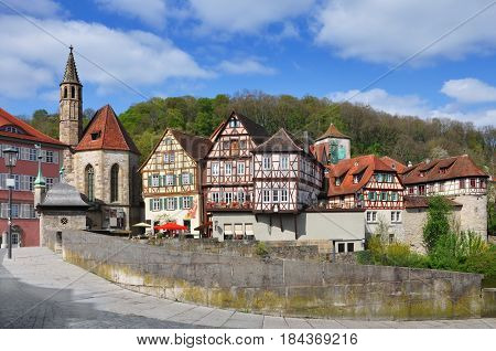 Quay Schwabisch Hall with a Gothic church of St. John and half-timbered houses at sunny day. Baden-Wurttemberg, Germany.