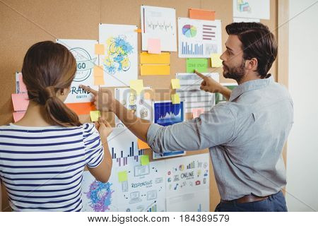Male and female executives discussing over bulletin board in office