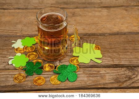 Mug of beer, chocolate gold coins and shamrock for St Patricks Day on wooden table