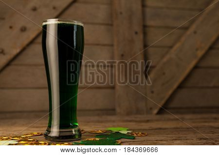 Glass of green beer, chocolate gold coins and shamrock for St Patricks Day on wooden table
