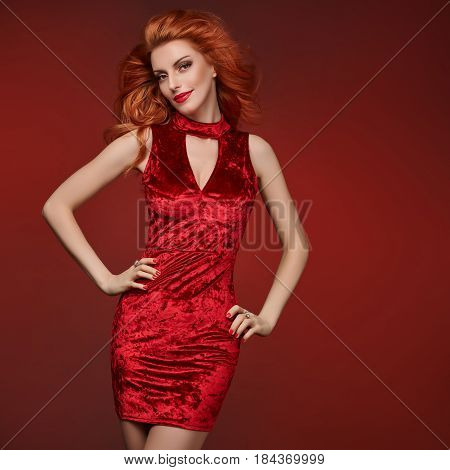 Fashion Beauty woman in Glamour Red Dress. Stylish Luxury Party Girl, Makeup. Redhead Sexy Model, Fashion wavy Hairstyle, Trendy Shine red Outfit. Playful Night Out Lady, fashion Pose. Creative Outfit