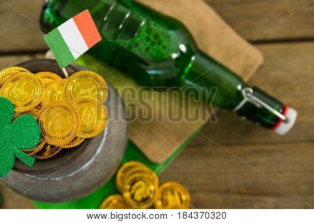 St. Patricks Day shamrock, flag, beer bottle and pot filled with chocolate gold coins on wooden table