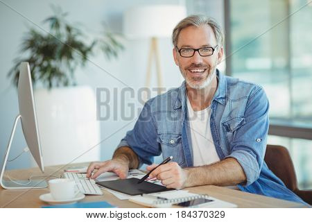 Portrait of male graphic designer using graphics tablet in office