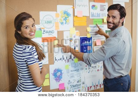 Portrait of two executives discussing over bulletin board in office