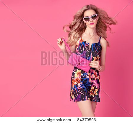 Fashion Blond Model in Sexy Jumpsuit, woman in Trendy Summer Dress. Stylish wavy hairstyle, fashion Sunglasses, Summer Floral Outfit. Glamour fashion pose. Playful Beauty Girl, Luxury summer Pink Clutch