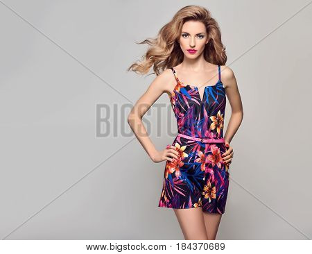 Fashion Beauty woman in Trendy Summer Dress. Stylish wavy hairstyle, fashion Makeup, Summer Floral Outfit. Glamour Blond Model in Sexy Jumpsuit, fashion pose. Playful Girl, Luxury summer Accessories