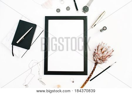 Blogger or freelancer workspace with blank screen photo frame protea flower notebook watches and feminine accessories on white background. Flat lay top view minimalistic decorated home office desk.