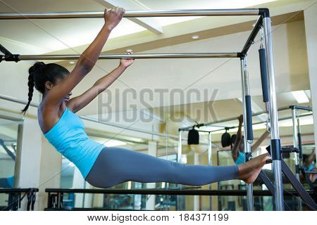 Determined woman performing stretching exercise on pilates cadillac in gym