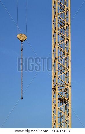 Closeup of yellow jib crane against blue sky