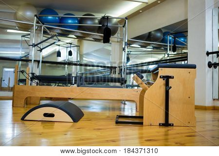 Various gym equipments on wooden floor in gym