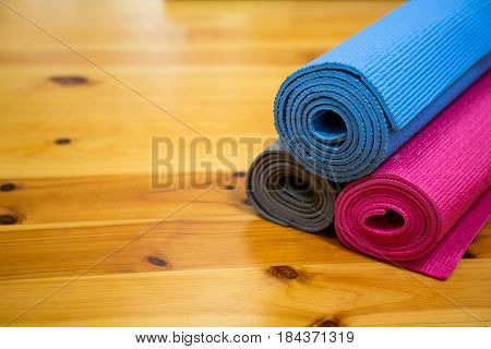 Rolled-up exercise mat on wooden floor in gym