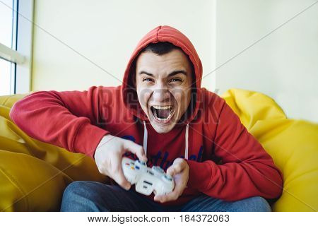 Emotional gamer sitting on the couch and playing video games using a gamepad. Focused view of the camera