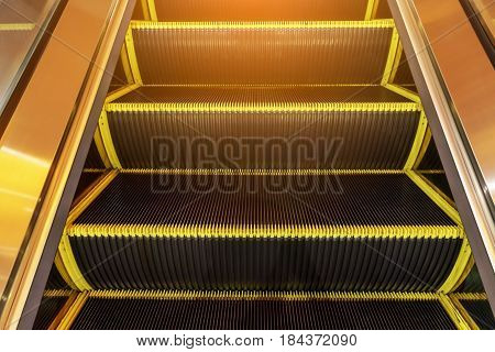 Electric escalator in yellow bands and metal line steel