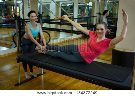 Portrait of female trainer assisting woman with stretching exercise on reformer in gym