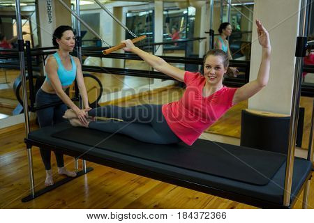 Female trainer assisting woman with stretching exercise on reformer in gym