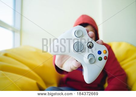 A young gamer shows a white gamer gaming joystick close up. Concept Video Games