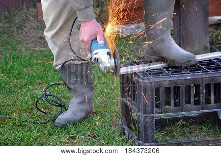 The process of cutting and polishing metal products at home. A man with an electric saw and sparks.
