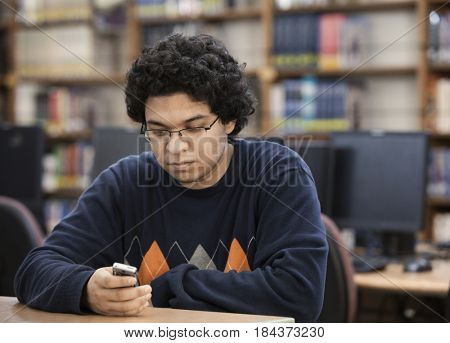 Filipino student with cell phone in school library