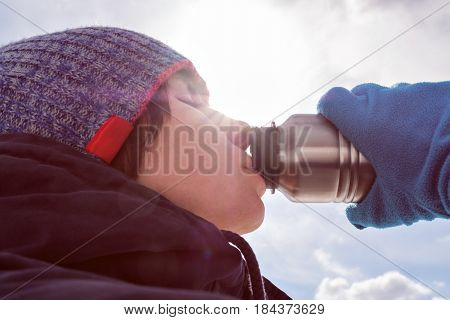 A girl in winter clothes eagerly drinks water from a bottle.