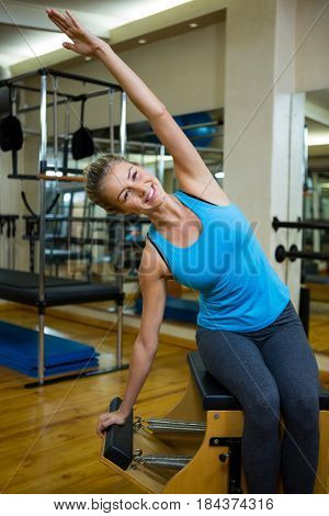 Portrait of determined woman exercising on wunda chair in gym