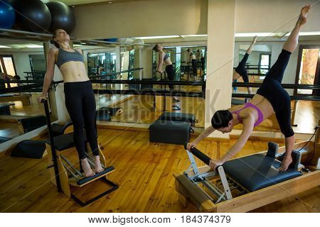 Determined woman practicing stretching exercise in gym