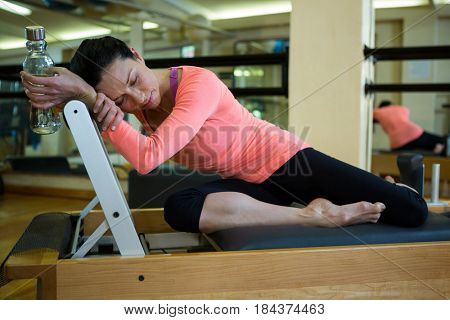 Tiered woman holding water bottle and relaxing on reformer in gym