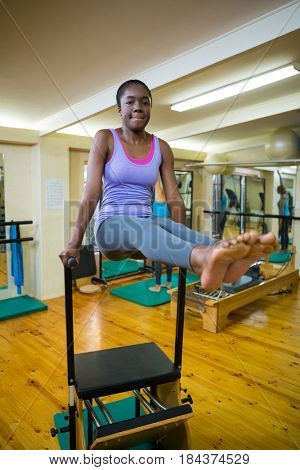 Portrait of woman exercising on wunda chair in gym