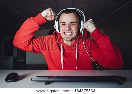 Joyful young man with headphones at home playing a computer game. Gamer happy for the win. Happy young man in headphone uses a computer. Gamer plays games on the computer
