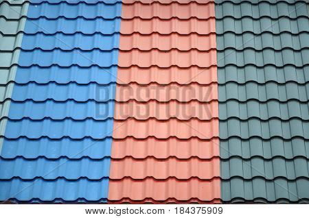 Architectural background. Texture of a metal roof tiles of black blue and red colors.