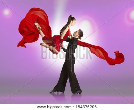 Beautiful couple ballroom dancing on illumination background