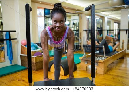 Portrait of fit woman exercising on wunda chair in gym