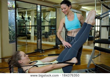 Female trainer assisting woman with stretching exercise in gym