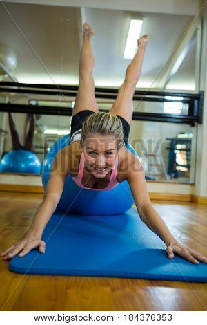 Portrait of fit woman performing pilate on exercise ball in fitness studio