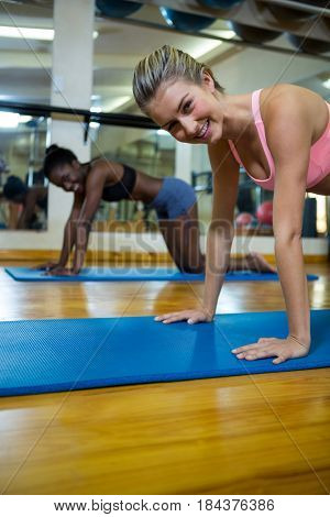 Portrait of two fit women doing stretching exercise on mat in fitness studio
