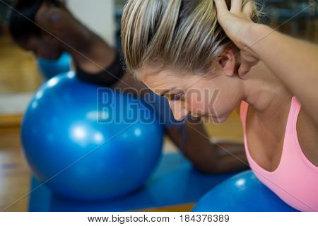 Smiling fit woman performing pilate on exercise ball in fitness studio