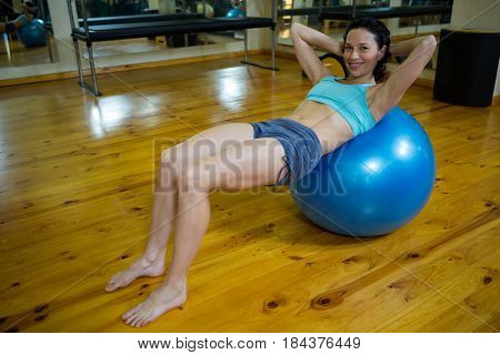 Portrait of happy woman exercising on fitness ball in gym