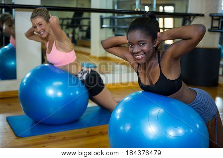 Portrait of two smiling women performing pilate on exercise ball in fitness studio