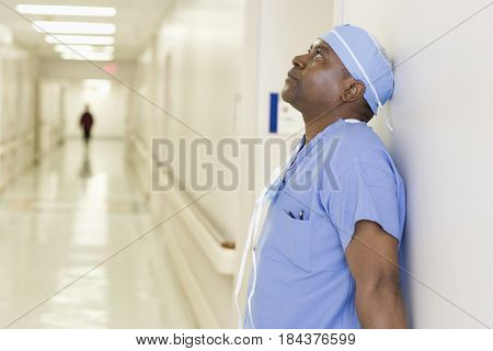 Black surgeon in scrubs in hospital hallway